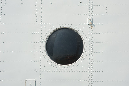 aircraft rivets: photographed close-up of metal siding and porthole in military plane in gray.