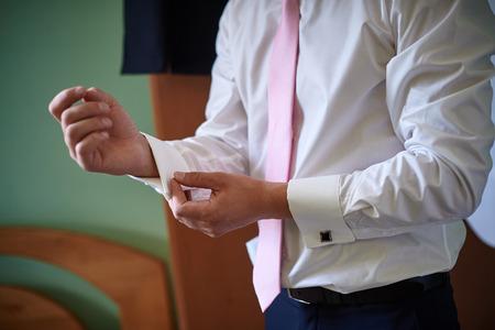 wrist cuffs: men wear white shirt and cufflinks in room