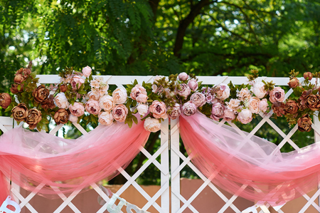 wedding arch decorated with flowers in the garden for the ceremony. Stock Photo