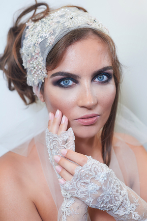 fashion studio portrait of beautiful young bride with make up and in elegant gloves.