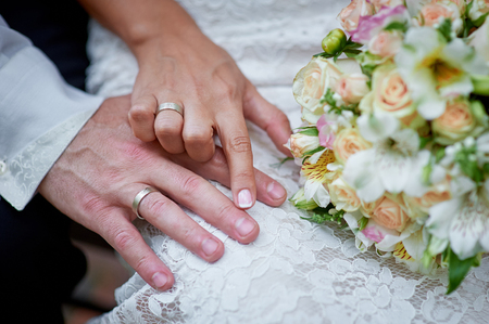 hands of the bride and groom with rings and wedding bouquet.