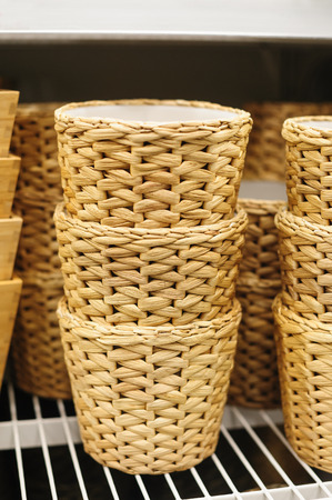 straw twig: woven straw baskets on a shelf in a store. Stock Photo