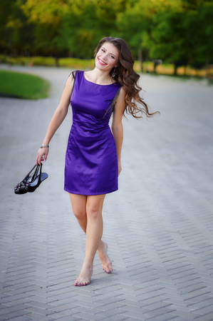 beautiful young woman holding shoes in her hands and walks in park Stock Photo