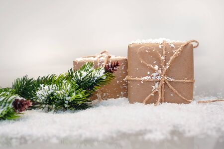 gift boxes and fir branches on artificial snow and place for text