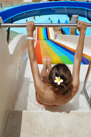 young woman slide down at the water park.