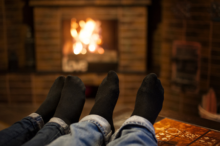 keeping room: Close up of romantic legs in socks in front fireplace