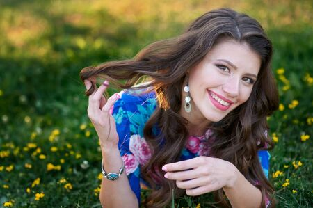 smiling young woman lying on the grass in the summer Park Stock Photo