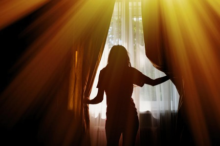 silhouette of young woman looking out the window Banque d'images
