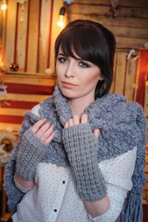 muffle: beautiful young woman with grey knitted scarf in the Studio