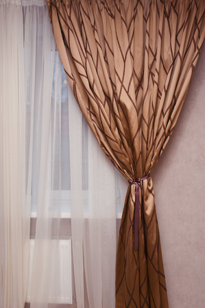 brown fabric curtain on the window in the bedroom Stock Photo