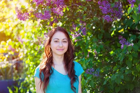 young woman near the lilac bush in the spring park. Stock Photo