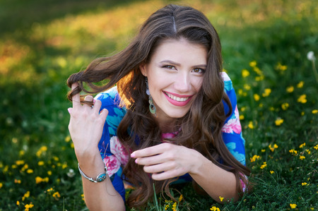 brown-haired woman smiles in a summer green glade with flowers Stock Photo