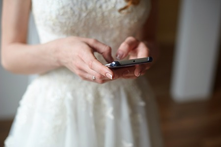 bride with the phone typing a message