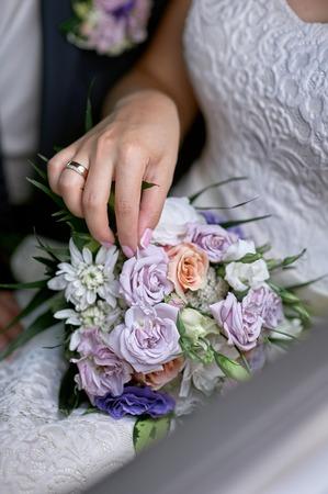 bride put her hand on the wedding bouquet