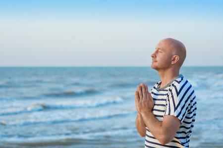 남자는 바다에 서서 하나님 께기도하고있다.