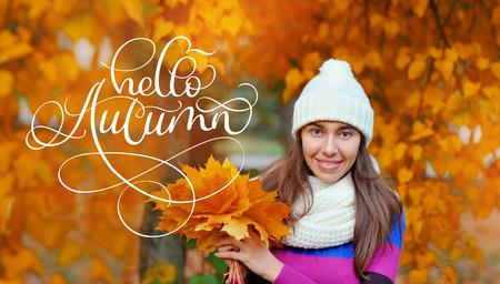 Hello Autumn calligraphy lettering text on Beautiful autumn woman in golden park Stock Photo