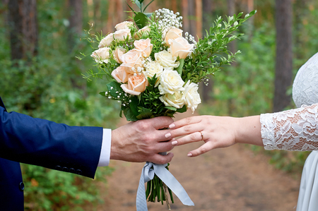 bridegroom gives the bride a wedding bouquet for a walk in the park Stock Photo