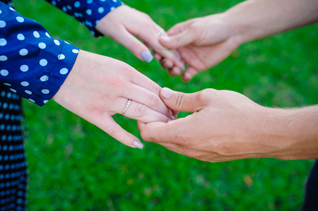 tenderly: two pairs of hands in love tenderly hold together on green grass background
