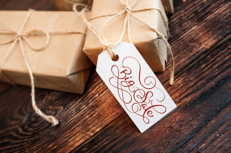web marketing: Two gift boxes and tag with Big Sale text on kraft paper and wooden background. Hand written calligraphy and lettering Stock Photo