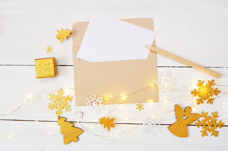 Christmas background with place for your text and golden christmas tree, garland and angel on a white wooden background. Flat lay, top view photo mockup
