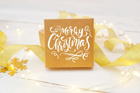 text Merry Christmas on the box of the craft, with gold ribbons and snowballs. Photography for holiday greeting card, invitation, calendar poster banner