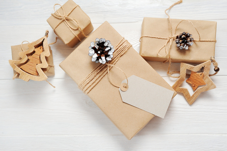 Mockup Christmas present gift box and tag on wooden background in vintage style. Flat lay, top view photo mock up