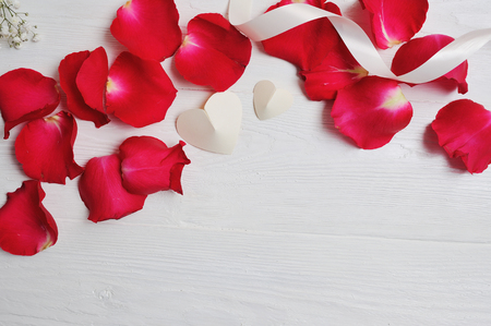Mockup Rose petals with two white hearts on a white wooden background, card Valentines Day. Flat lay, top view with a place for your text