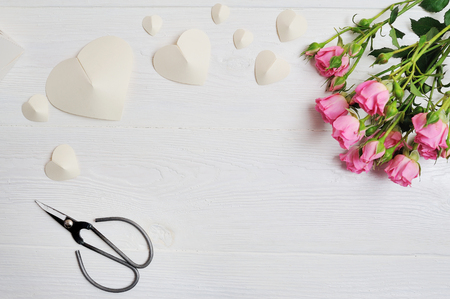 Mockup white origami hearts made of paper with pink roses and scissors, card for Valentines Day. Flat lay, top view with a place for your text Stock Photo