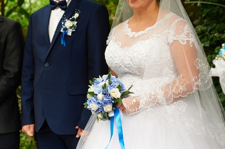 beautiful bridal bouquet of roses and hydrangeas on the background bride and groom stand at a wedding ceremony