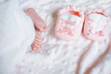 Bare feet of a cute newborn baby in warm white blanket. Childhood. Small bare feet of a little baby girl. Sleeping newborn child.