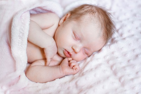 텍스트를 넣을 수 있는 분홍색 담요에서 자고 있는 사랑스러운 갓난 소녀 스톡 콘텐츠