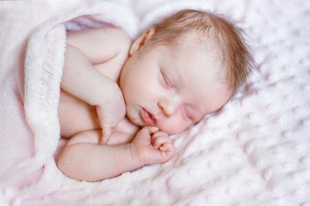 Encantadora niña recién nacida durmiendo en una manta rosa con lugar para el texto Foto de archivo
