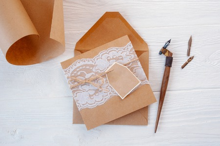 Mockup holiday letter Blank paper and an envelope with pen on wood table, with space for your text, top view.