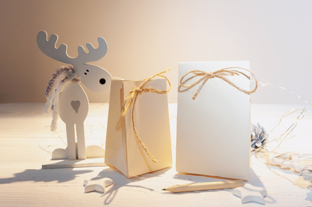 mockup of two Christmas kraft gift packages with tag on wooden background. Top view for greeting card.