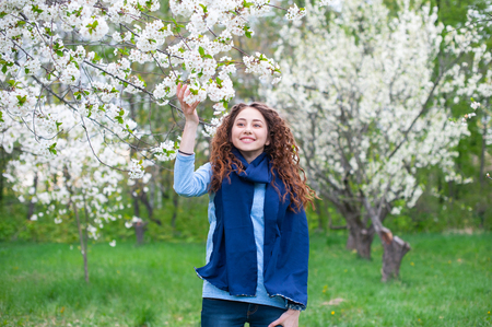 Portrait of a young beautiful fashionable woman in spring blossoming park. Happy girl posing in a blooming garden with white flowers.