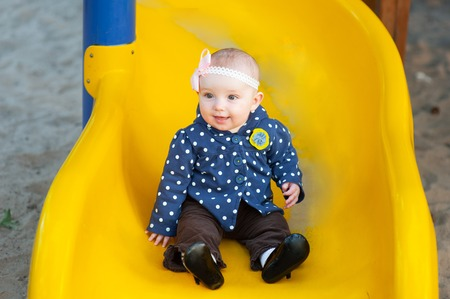 girl two years old brunette in jacket riding on a yellow hill on the playground in the park. Imagens