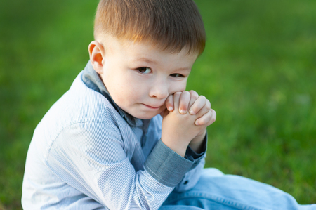 Cute boy is sitting on green grass. He is waiting. Concept of childrens happy.
