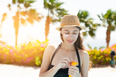 beautiful woman smears face sunscreen at the beach for sun protection. Stock Photo