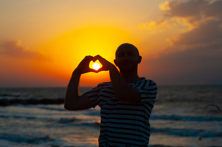 male hands in the form of heart against the sky pass sun beams. Hands in shape of love heart.