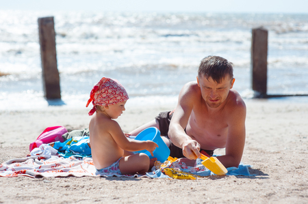 Father and daughter on beach playing and building sand castle.