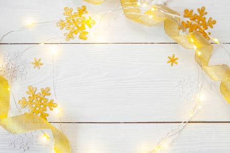 Weihnachtshintergrund für Grußkarte mit Platz für Text. x-mas goldenes Spielzeug und Band auf Holzuntergrund. Flache Lage, Fotomodell in Draufsicht.