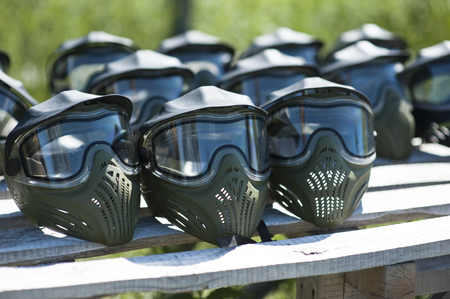 Special protective mask for playing paintball with traces and spot of hit of a ball with paint. Equipment for playing paintball on a wooden table. Game marker and a protective mask. Image photography. Stock Photo