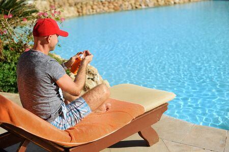 Young and successful man on a sun lounger squeezes out sunblock cream from a tube at the hotel near sweeming pool. Concept summer time to travel Stock Photo