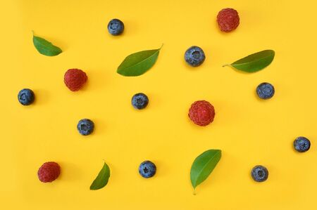 Summer blueberries and raspberries with leaf on yellow background. Berries design backdrop. Close up top view or flat lay