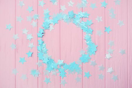 Blue stars confetti on a pink wooden background with round frame place for your text, design greeting cards and invitation