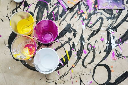 plastic cups with magenta, yellow and white acrylic colors. Abstract color liquid acrylic art on kraft paper background. Hand drawing art. self made Reklamní fotografie