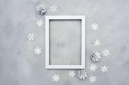 Marco de Navidad de fotos en blanco con lugar para el texto. Maqueta de vacaciones. copos de nieve y conos sobre fondo gris. Plantilla de tarjeta de felicitación de año nuevo. Estilo escandinavo Foto de archivo