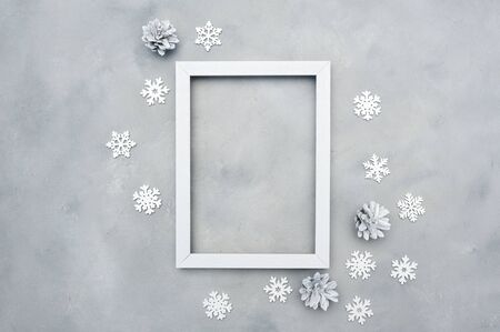 White photo christmas frame with place for text. Holiday mock up. snowflakes and cones on the grey background. New year greeting card template. Scandinavian style