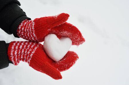 Manos femeninas en guantes de ganchillo rojos cálidos con corazón nevado. Fondo de nieve blanca. Concepto de amor. Tarjeta de felicitación del día de San Valentín con copyspace