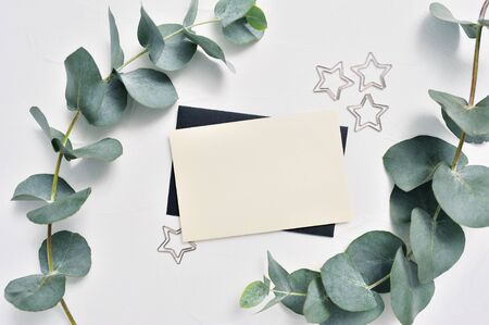 Mock up of Eucalyptus leaves and decor of stars paper clip with place for text on white background. Wreath made of eucalyptus branches. Flat lay, top view